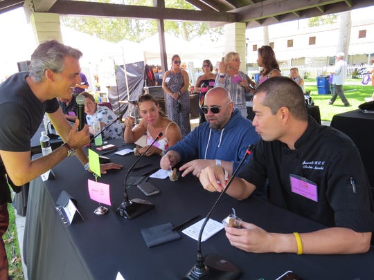 Duff Goldman chats with emcee Oded Fehr, left, and fellow chefs Robin Atkin, in a sundress, and Robin Nishizaki, far right, while helping judge the Yummie Top Chef Awards at the Casa Pacifica Angels Food, Wine & Brew Festival in Camarillo in 2015.