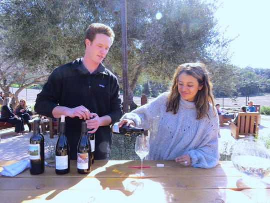 Nick Rudolph and Marie Holguin van Leewen keep the wine flowing during an event for Old Creek Ranch Winery wine-club members in February. The property located between Ojai and Ventura will reopen to the public on April 7.