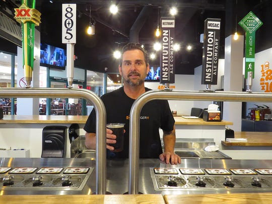 Michael Nunes, owner of Burgerim at the Camarillo Premium Outlets, poses with the restaurant's Bottoms Up draft-beer system around the time of the restaurant's opening in 2018.