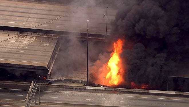 A large fire that caused an overpass on Interstate 85 to collapse burns in Atlanta, . Witnesses say troopers were telling cars to turn around on the bridge because they were concerned about its integrity. Minutes later, the bridge collapsed.