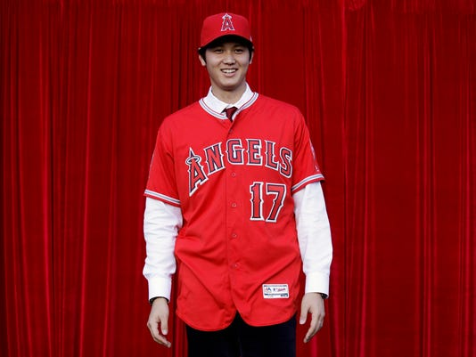 Baseball player Shohei Ohtani, of Japan, poses for photos after a news conference at Angel Stadium, Saturday, Dec. 9, 2017, in Anaheim, Calif. Ohtani, who intends to be both a starting pitcher and an everyday power hitter, turned down interest from every other big-league club to join two-time MVP Mike Trout and slugger Albert Pujols with the Angels, who are coming off their second consecutive losing season and haven't won a playoff game since 2009. (AP Photo/Jae C. Hong)
