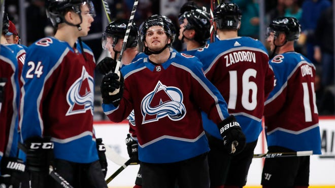 Colorado Avalanche center Alexander Kerfoot, center, celebrates with teammates as they salute fans after an NHL hockey game against the Anaheim Ducks Monday, Jan. 15, 2018, in Denver. The Avalanche won 3-1. (AP Photo/David Zalubowski)