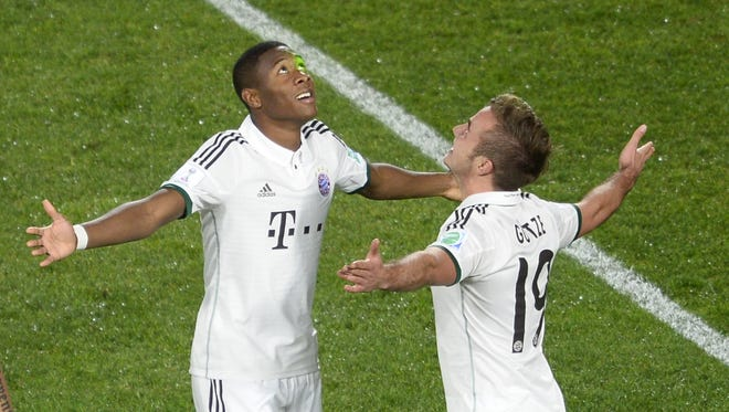 Bayern Munich midfielders Mario Goetze, right, and David Alaba celebrate after Goetze scored the third goal against Guangzhou Evergrande FC during Tuesday's Club World Cup semifinals.