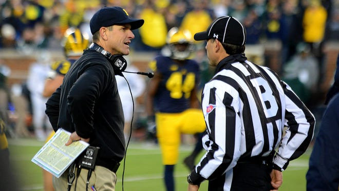 Michigan coach Jim Harbaugh talks with a referee during the game Saturday, October 17, 2015 at Michigan Stadium in Ann Arbor. Michigan State won 27-23.