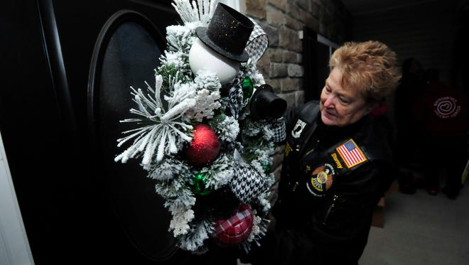 Judy LaPlante, of American Legion Post 46 Legion Riders, lays a wreath on the door Tuesday, Nov. 24, 2015. The group along with Helping Little Hands and other volunteers decorated wounded veteran Zach Stinson's Guilford Township house for Christmas. This is the third holiday season the group has helped with decorations.