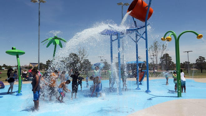 A large bucket of water spills onto waiting kids Tuesday afternoon at the Marty Robbins Spray Park at 11600 Vista Del Sol Drive as the temperature reached the triple-digit mark.