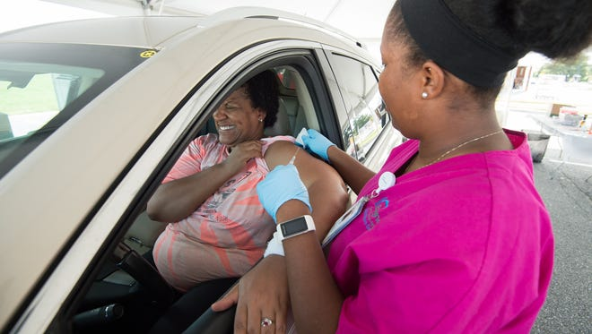 Leah Porter of Dover closes her eyes as Kayla Giddens, BSN, RN, with BayHealth gives her a flu shot at the Division of Public Health's drive-thru flu vaccination clinic at the DelDOT Administration Building in Dover.