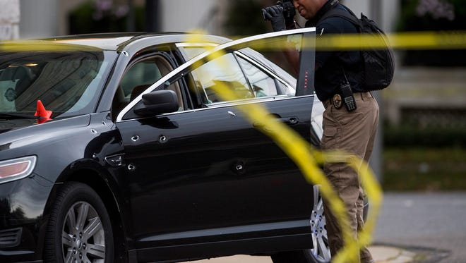 Montgomery Police work the scene of a shooting on Scott Street next to first Baptist Church in downtown Montgomery, Ala. on Monday evening October 23, 2017. Bullet holes can be seen in the side of the car.