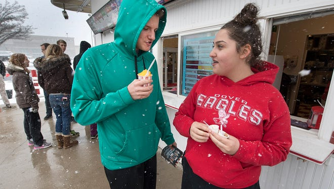 Dylan Jacobson, left, and Zoe Nahum get their free Rita's Italian ice on the first day of spring at the Manchester Crossroads Shopping Center in Manchester Township. The Dover Area High School students got out early from classes because of the snow.