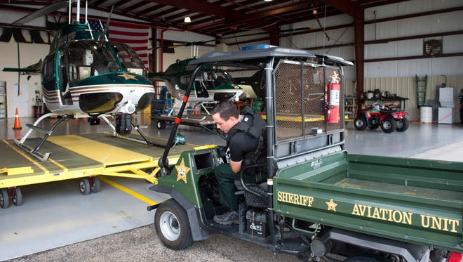 Martin County Sheriff's deputy and tactical flight officer, Robert Calarco pulls out a sheriff's helicopter as he and pilot, Doug Newsom (not pictured) prepare to go out on a call Tuesday, Sept. 13, 2016 in Stuart.  Within the last year the sheriff's office made significant upgrades to the helicopter's camera and mapping system.