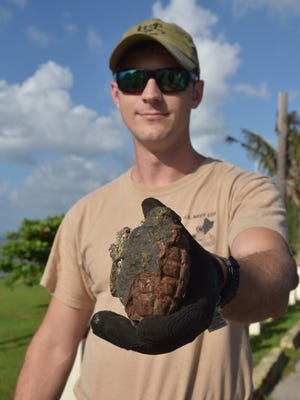 Naval Petty Officer 1st Class Charles Brown, assigned to the Explosive Ordnance Disposal Detachment Marianas at Naval Magazine Guam, holds out a World War II-era U.S. Mark II fragmentation grenade recovered at the Asan Memorial Beach Park on Thursday, May 3, 2018. The ordnance was found by a woman fishing in the waters off the beach and she reported the find to the Asan-Maina mayor's office who called emergency responders to handle the situation.