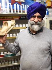Amrik Singh, owner of Staatsburg Citgo in Hyde Park shows the sandal that he threw at a would be robber on Wednesday. The assailant fled the store after Singh confronted the man Tuesday night.