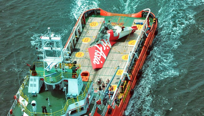 An aerial photo shows a tail section of the AirAsia flight QZ8501 on the deck of a Crest Onyx ship as the search for black boxes of the aircraft continues.