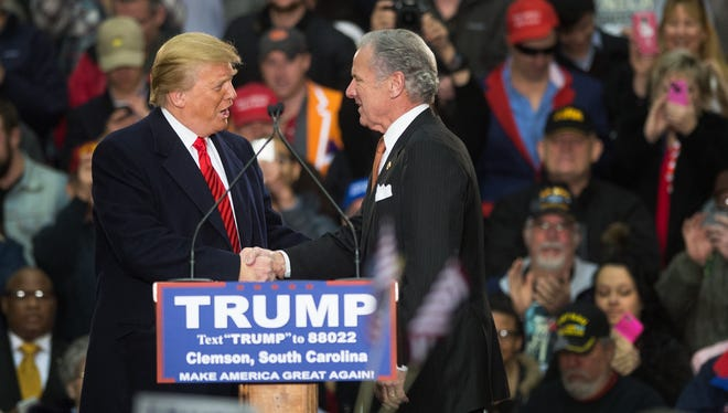 Donald Trump shakes hands with then-Lieutenant Governor Henry McMaster during a rally at the T. Ed Garrison Livestock Arena in Clemson on Wednesday, February 10, 2016.