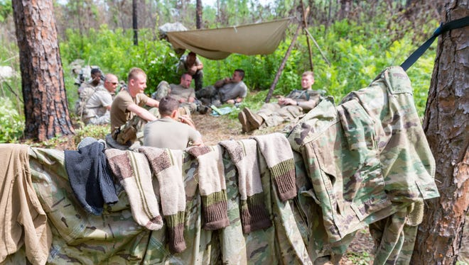 Soldiers from 256th 2nd Battalion Alpha Company take a break from the heat and dry out socks before a platoon attack exercise during XCTC Training at Camp Shelby, Mississippi on July 20, 2018.