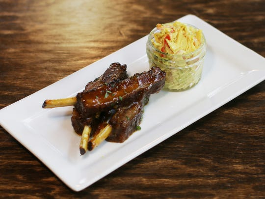 Wild boar ribs feature St. Louis-style cuts of meat glazed in Bombay sauce with curry slaw.