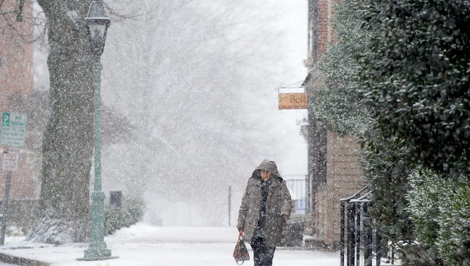 A person walks in The Green in Dover on Wednesday afternoon as snow begins to fall.