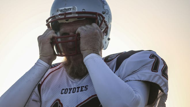 Former USC and Oakland Raiders quarterback Todd Marinovich, 48, puts on his SoCal Coyotes helmet during the teams' first practice at Shadow Hills High School in Indio on Saturday, August 12, 2017.