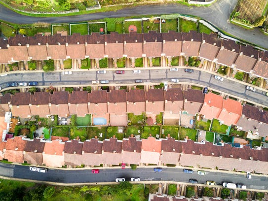 Aerial view of suburban houses with small back yards.