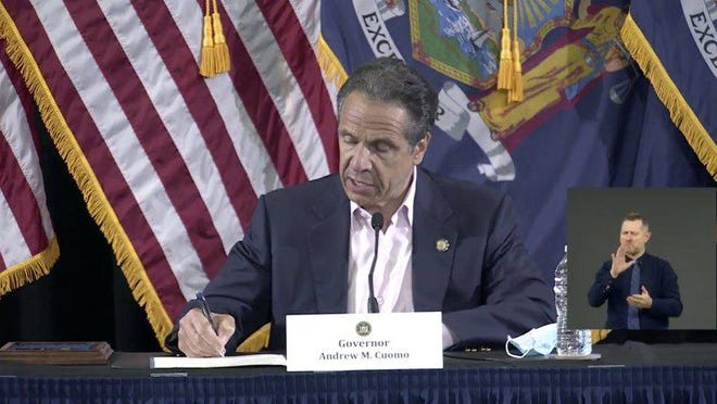 In this image made from video provided by the office of Gov. Andrew M. Cuomo, Gov. Cuomo signs a bill giving death benefits to the families of certain government workers who were killed by coronavirus, Saturday, May 30, 2020 in New York.