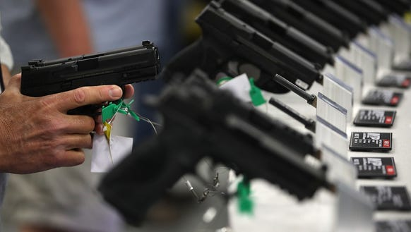 Smith and Wesson handguns are displayed during the