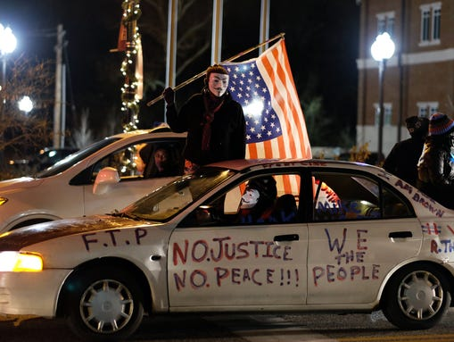 Demonstrators ride a car past the police station in