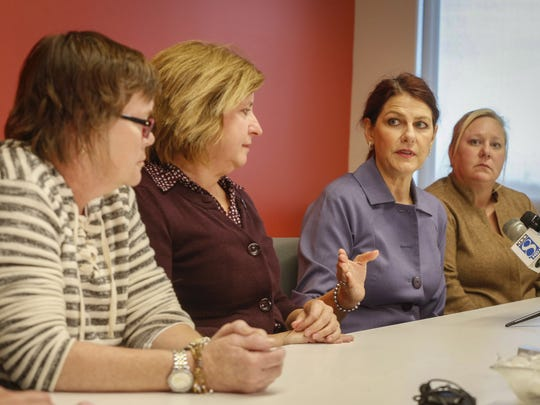 Johnston attorney Paige Fiedler, second from right, speaks to members of the press regarding a settlement between her clients, former employees at the West Des Moines police department, and the city of West Des Moines during a conference on Tuesday, Nov. 15, 2016, in Johnston.