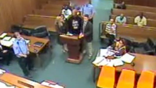 A photo taken from video show man (in black shirt) being sentenced right before his death.