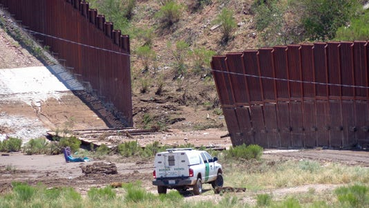 A border-patrol vehicle is seen near a section of collapsed fence just west of the Mariposa Port of Entry in Nogales, Ariz.