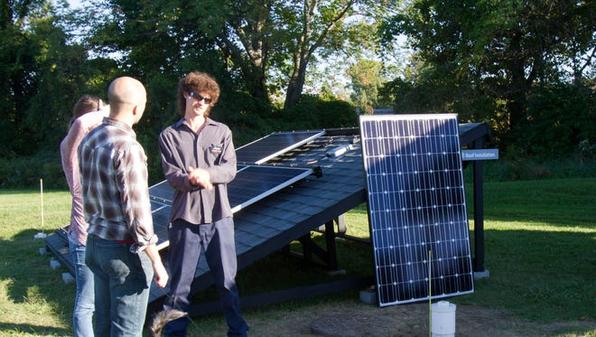 Jesse Woodbury of Renovus Solar of Ithaca demonstrates the roof-array mockup at the company's open house Wednesday.