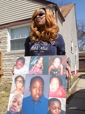 Standing outside her Pontiac home on Tuesday, April 10, 2018, Cyrria Mims holds a posterboard display of photos of her younger brother, Omarion Humphrey, who drowned while in foster care in 2015.