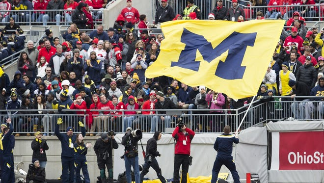 A Michigan cheerleader waves the flag in front of Ohio State fans on Nov. 29, 2014.