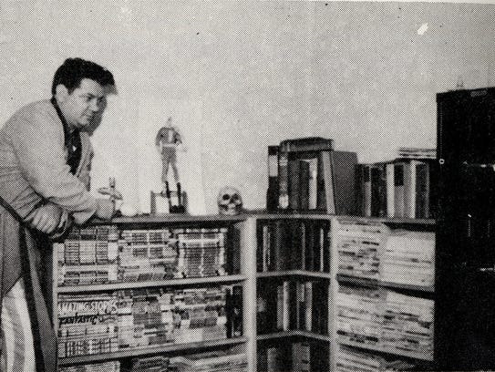 Otto Binder standing near some shelves in his office