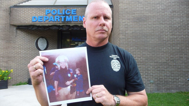 Detective Ken Arnold holds a photo of Brandy Hall