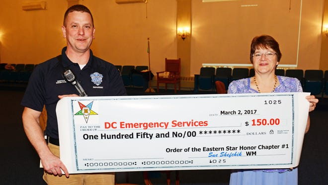 Aaron LeClair, deputy director of Door County EMS, poses with a sign of a check given to the agency by Mariellen Haen of the Sturgeon Bay Order of the Eastern Star Chapter.