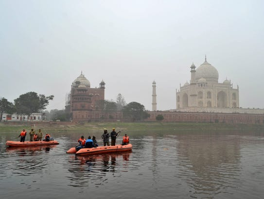 Indian policemen patrol the Yamuna River passing the