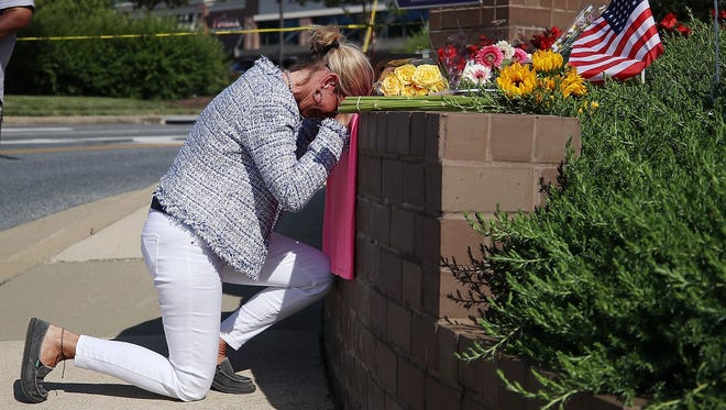 Lynne Griffin pays her respects at a makeshift memorial near the Capital Gazette where 5 people were shot and killed by a gunman on Thursday, on June 29, 2018 in Annapolis, Md.