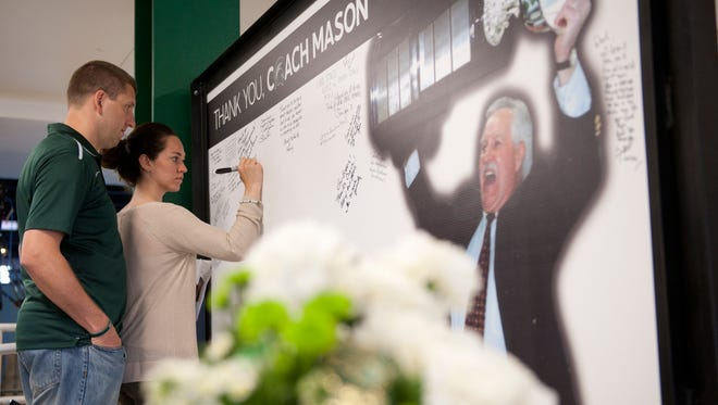 Haslett residents Jon Legg and Jessica Rademacher sign a large thank you card during the funeral service for Coach Ron Mason on Thursday, June 16, 2016 at Munn Ice Arena. Mason was a former Michigan State hockey coach and athletics director. Mason led the Spartans to the 1986 NCAA national championship and molded MSU into a leading hockey program, going 635-270-69 in 23 seasons. Under him, the Spartans went to the NCAA tournament 19 times, won seven CCHA regular-season titles and 10 league post-season tourney titles.