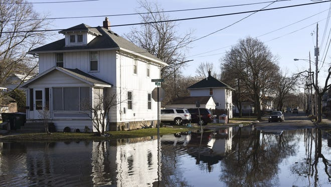 In this Thursday, Feb. 22, 2018 photo, the intersection of Ada and Beulah Streets is flooded in the Baker-Donora neighborhood in Lansing, Mich. Flooding that prompted evacuations in parts of the Midwest persisted Friday in Michigan, Indiana, and Ohio and was expected to last through the weekend in areas that have been swamped by high water from heavy rains and melting snow.