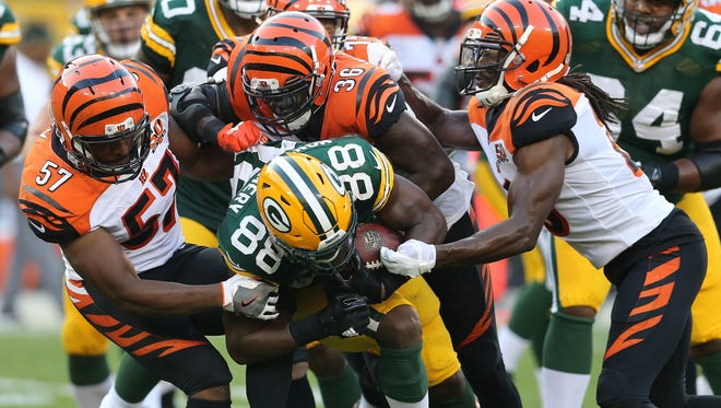 Green Bay Packers running back Ty Montgomery (88) is gang tackles by Cincinnati Bengals outside linebacker Vincent Rey (57), strong safety Shawn Williams (36) and cornerback Josh Shaw (26) in the fourth quarter during the Week 3 NFL football game between the Cincinnati Bengals and the Green Bay Packers, Sunday, Sept. 24, 2017, at Lambeau Field in Green Bay, Wisconsin.
