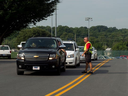 An officer directs incoming traffic arriving for move-in