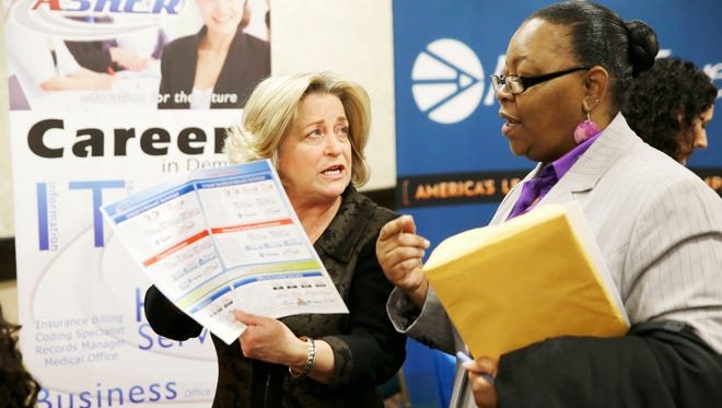 Recruiter Valera Kulow, left, speaks with job seeker Monic Spencer during a career fair in Dallas on January 22, 2014.