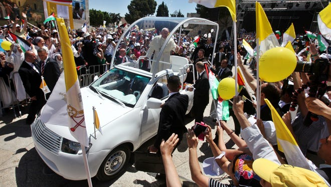 Pope Francis waves to faithfuls upon his arrival to lead an open-air Mass in the Manger Square, next the Nativity Church, in the West Bank city of Bethlehem, on May 25, 2014.