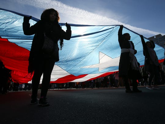 A group of protesters carry the flag of Puerto Rico as they take part in the Women's March in Philadelphia Saturday morning.