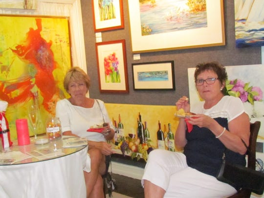 Susan Scharles and Jane Prather relax among the artwork during First Friday open house.