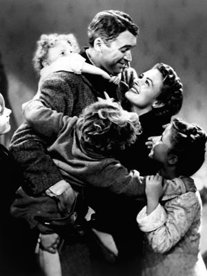 Jimmy Stewart and Donna Reed with other cast members in a scene from the motion picture 'It's a Wonderful Life.'