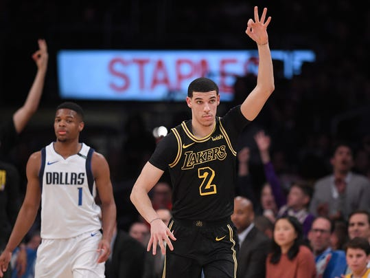 Los Angeles Lakers guard Lonzo Ball, right, gestures after hitting a 3-point shot as Dallas Mavericks guard Dennis Smith Jr. stands behind during the first half of an NBA basketball game Friday, Feb. 23, 2018, in Los Angeles. (AP Photo/Mark J. Terrill)