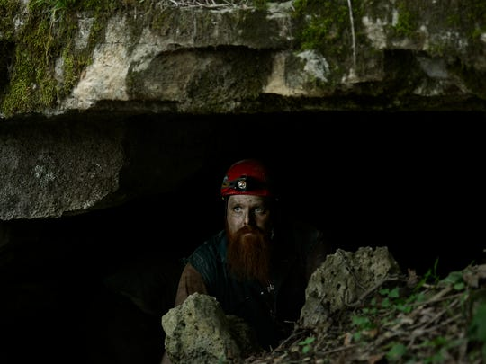 Cory Holliday, director of The Nature Conservancy's Tennessee cave program, waits inside a bat cave entrance while working on a gate.