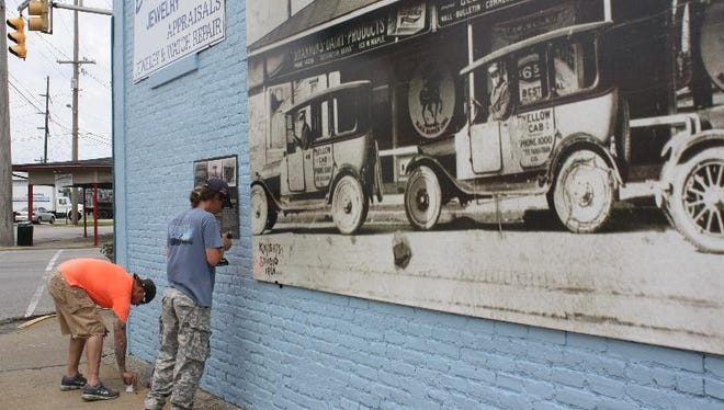 Justin Hansford, left, and Simon McLaughlin with S.K. Sign & Banner install signage for a Monumental Memories photo in downtown Jeffersonville on Tuesday.