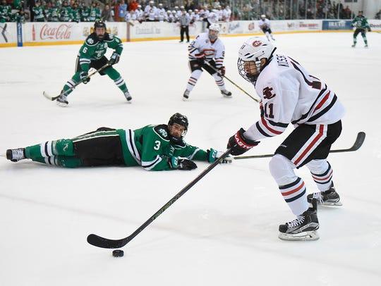 North Dakota's Tucker Poolman slides to the ice while